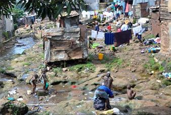 People washing adjacent to run-off from Dump Site