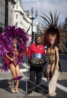 In Regent Street carnival dancers Jennice Crystal Price and Lolo Page from Trinidad and Tobago wearing costumes by Bacchanalia and steel pannist for CSI Steel band Dexter Yearwood
