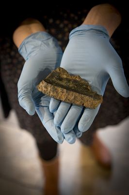 Person holding a fragment of the first gun barrel to be found on a medieval battleground