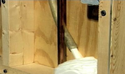 Insulation foam is injected into an existing wall cavity via a tube