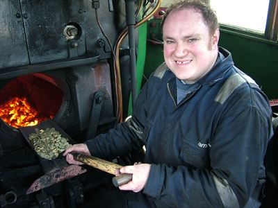 Adrian Dennis, steam locomotive fitter for the North Yorkshire Moors Railway with a shovel full of pound coins