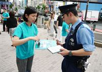 A Tokyo volunteer shows The Truth About Drugs portfolio to a police officer.