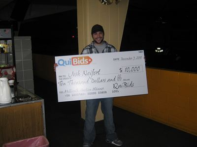 Winner Josh Neifert holding an oversized $10,000 check.