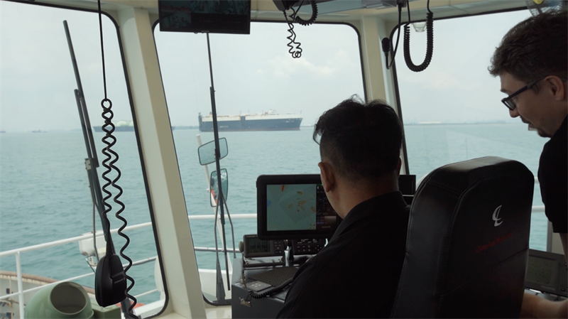 A PSA Marine Tug Master and Thomas monitoring how the smart navigation system manouevres the harbour tug during sea trials. Copyright: Wärtsilä.