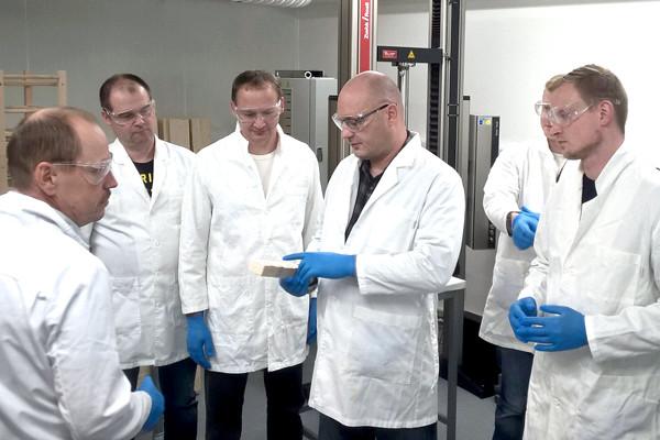 Pasi Honkapuro (keskellä) ja muut jatkojalostuksen työntekijät tarkastelevat liiman kovettumista liimakoulutuksessa Lempäälässä.