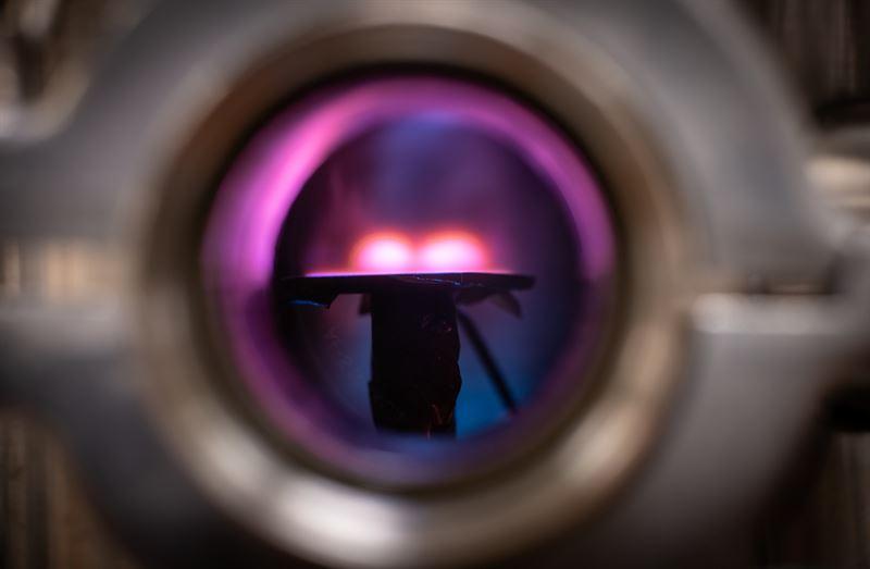En titt in i vakuumkammaren dr man ser plasmat ovanfr ytan dr metallfilmen skapas