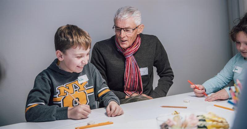 En volontr hjllper en elev under en skrivvning p Berttarministeriet