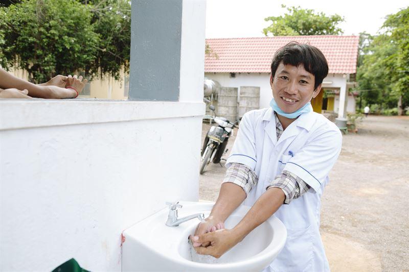 Nurse Peu Aranhya 30 washes his hands at a sink Thmor Kol Referral Hospital Battambang Cambodia  Photo WaterAidTom Greenwood